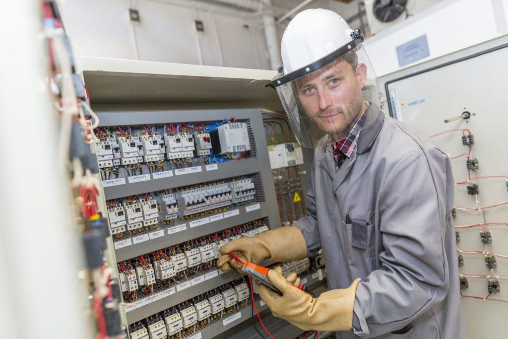 eletricista efetuando manutenção em um painel de elétrica industrial