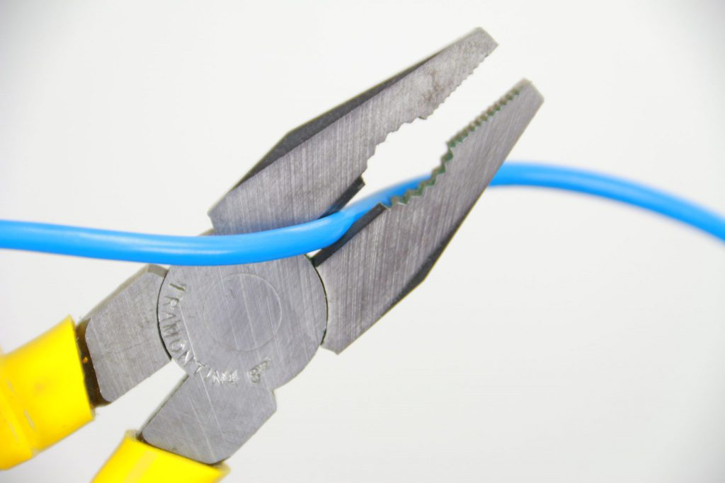 alicate universal cortando um fio neutro