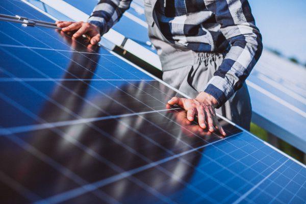 homem instalanco painel solar
